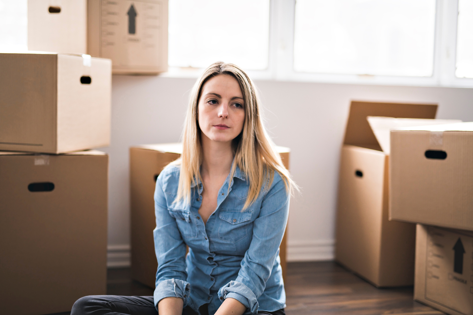 Woman in a room surrounded by boxes