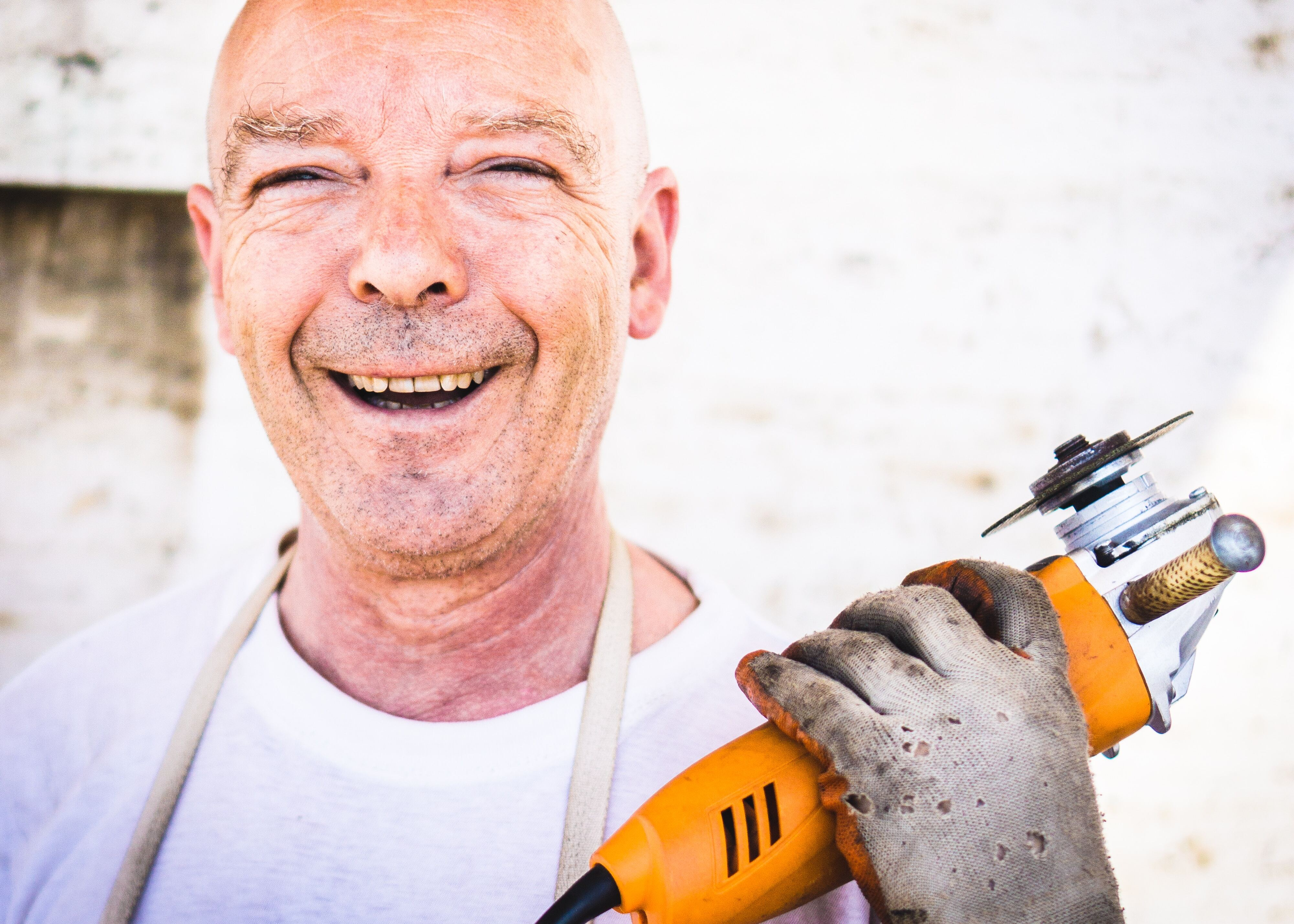mature man smiling into the camera holding a power tool