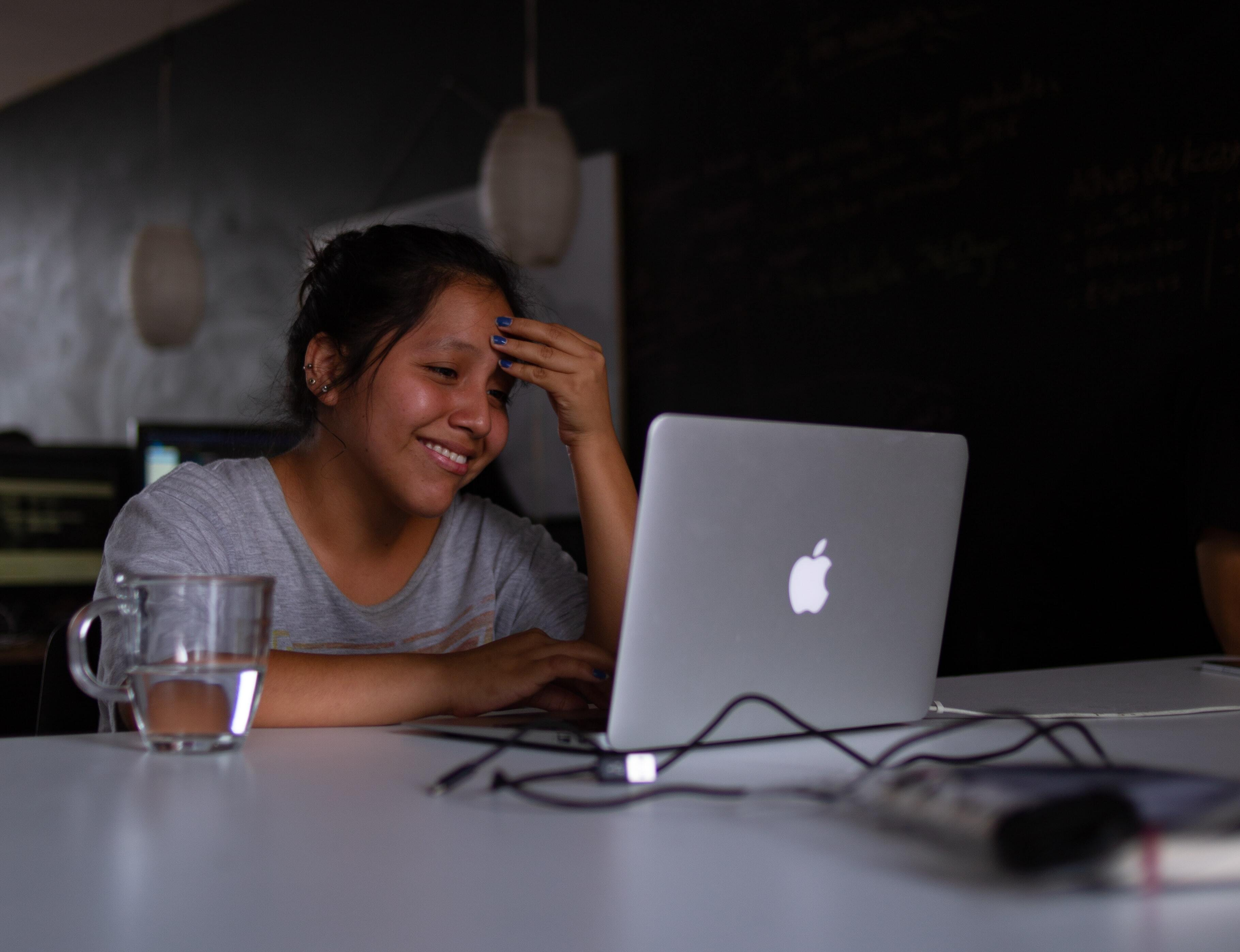 woman smiling while looking at computer