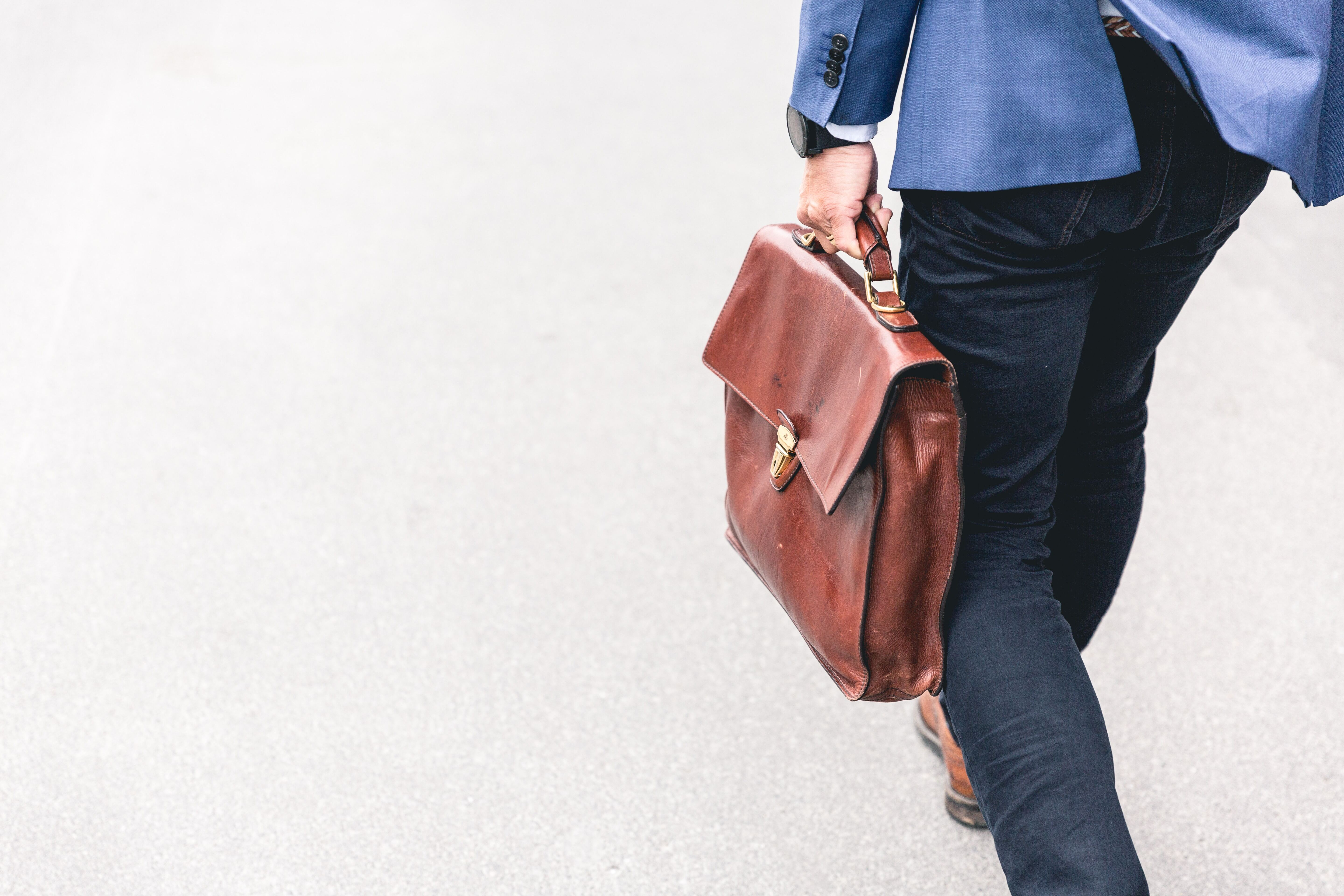 man walking with brown leather bag