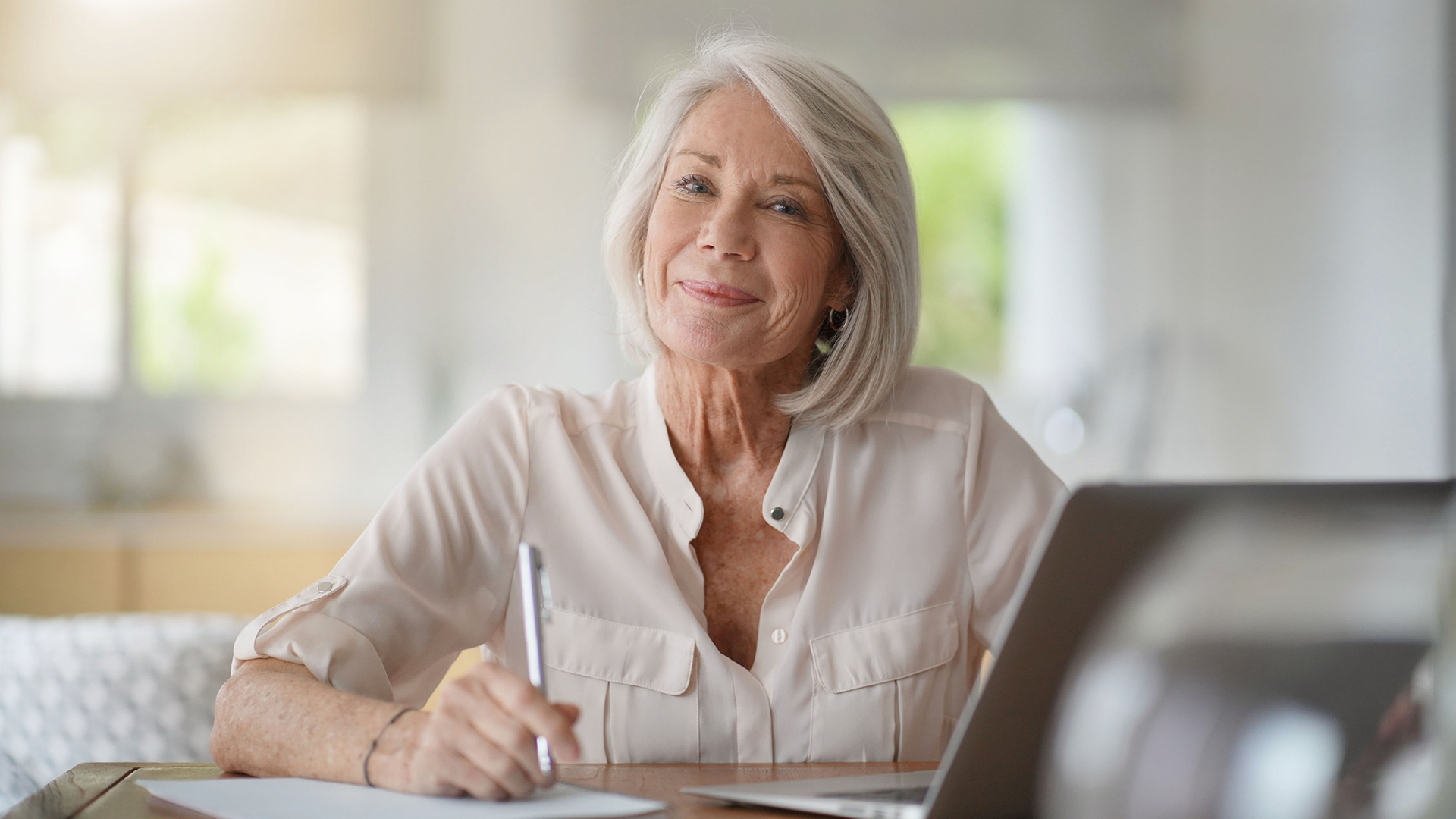 mature woman writing on paper at a desk looking at camera