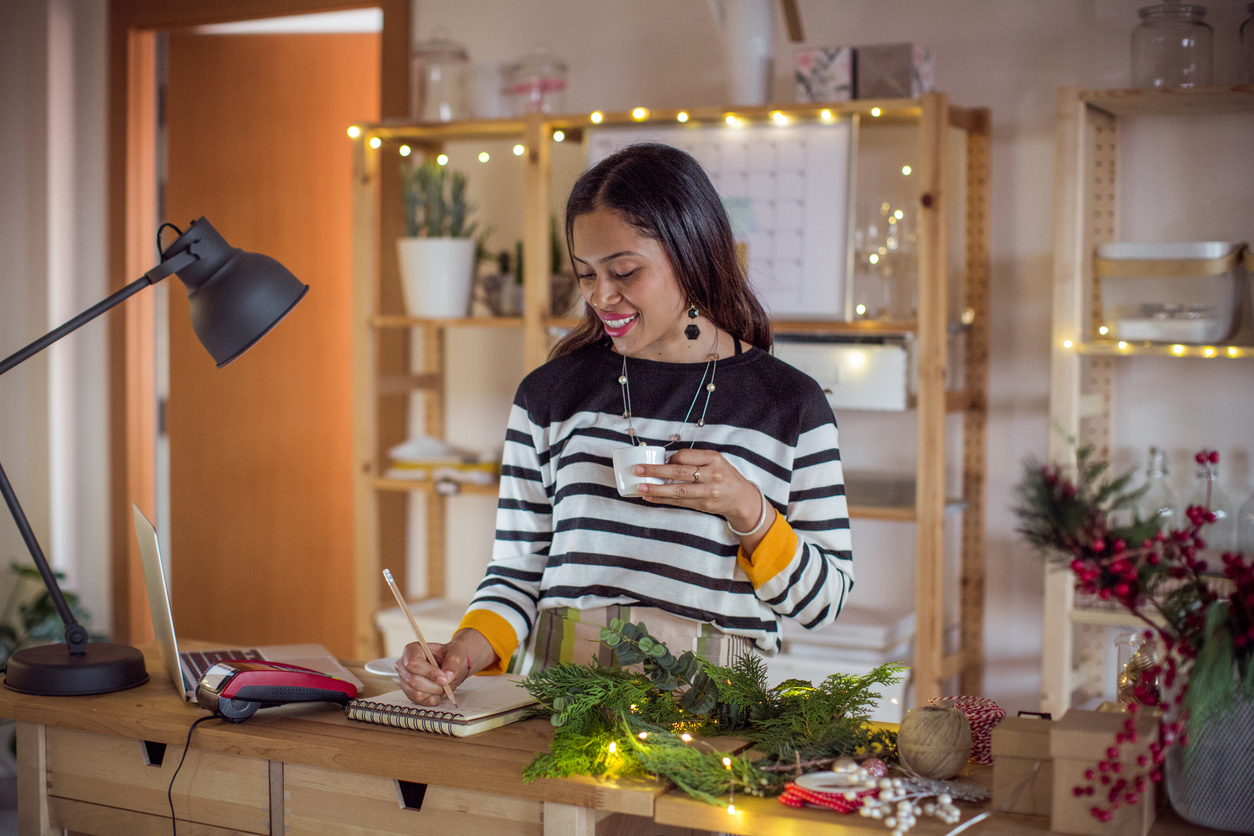 lady standing in front of laptop with Christmas lights in background