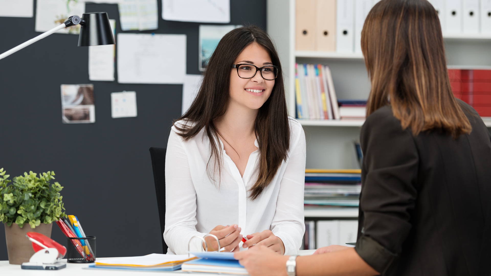 lady smiling at desk with employer