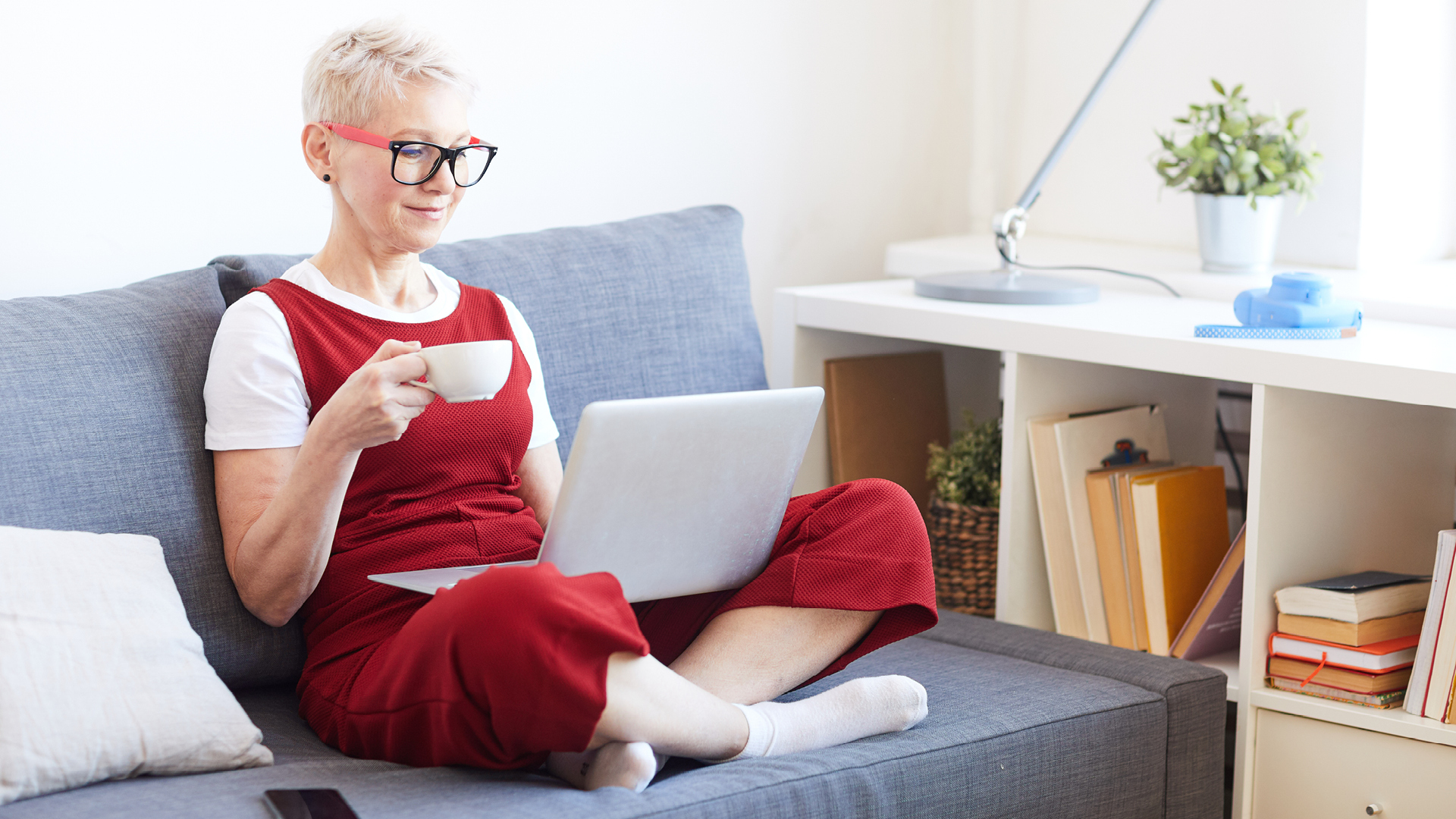 woman on couch looking at laptop